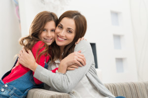 Portrait Of Happy Mother And Daughter Embracing Looking At Camera