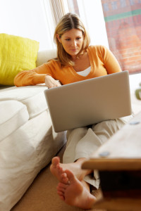 Young attractive Woman uses laptop at home whilst sitting on the lounge floor