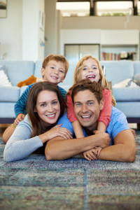 Cropped shot of an adorable family lying on the floor in their living room and smiling happily at the camera